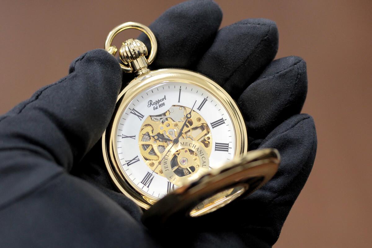 イギリスブランド rapport(ラポート) 懐中時計 pw48 ゴールドカラーの両蓋開きスケルトンモデルを手に持ったイメージ